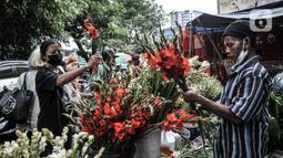 Pedagang menata bunga hias dagangannya saat menunggu pembeli di Pasar Petak Sembilan, Jakarta, Kamis (11/2/2021). Bunga hias yang dijual antara lain sedap malam, anggrek, krisan, dan lotus. (merdeka.com/Iqbal S. Nugroho)