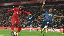 Gelandang Manchester United, Ashley Young, menghalau umpan gelandang Liverpool, Naby Keita, pada laga Premier League di Stadion Anfield, Liverpool, Minggu (16/12). Liverpool menang 3-1 atas MU. (AFP/Paul Ellis)