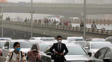 Warga mengenakan masker melewati kendaraan yang terjebak kemacetan saat badai debu di jalanan Beijing, Kamis (4/5). Badai debu menerjang utara China dan Beijing, serta membuat otoritas membatalkan puluhan penerbangan. (AP Photo/Andy Wong)