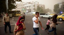 Sempat terjadi kepanikan, beberapa warga Iran terlihat berjalan di tengah-tengah debu pasir di Teheran, Iran, (2/6/2014). (AFP PHOTO/ISNA/Hamidreza Dastjerdi)