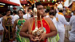Penganut kuil Loem Hu Thai Su menusukkan menusukkan teko besi ke pipinya saat festival vegetarian tahunan di Phuket, Thailand, Jumat (12/10). Acara ini diselenggarakan oleh komunitas keturunan Tionghoa di seluruh Thailand. (Jewel Samad/AFP)