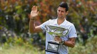 Petenis Serbia, Novak Djokovic memegang piala juara tunggal putra Australia Terbuka 2020 saat sesi pemotretan di Royal Botanic Gardens Victoria, Melbourne, Australia, Senin (3/2/2020). Bagi Novak Djokovic, ini merupakan gelar Australia Terbuka kedelapan. (Photo by William WEST / AFP)