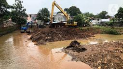 Petugas menggunakan alat berat untuk mengeruk lumpur serta memperlebar aliran Kali Krukut di kawasan Kemang, Jakarta, Selasa (10/11/2020). Pelebaran serta pengerukan tersebut bertujuan untuk memperlancar aliran air yang kerap menimbulkan banjir setiap hujan deras. (Liputan6.com/Immanuel Antonius)