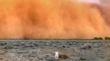 Foto  yang diambil 17 Januari 2020 dan diterima 20 Januari memperlihatkan seorang anak berlari menuju badai debu di Mullengudgery, New South Wales. Badai debu melanda banyak bagian barat New South Wales Australia ketika kekeringan berkepanjangan berlanjut. (Handout/Courtesy of Marcia Macmillan/AFP)