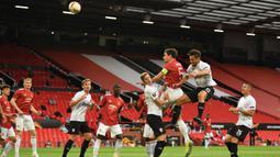 Bek Manchester United, Harry Maguire, berebut bola dengan pemain LASK pada laga leg kedua 16 besar Liga Europa 2019/2020 di Old Trafford, Kamis (6/8/2020) dini hari WIB. Manchester United menang agregat 7-1 atas LASK. (AFP/Oli Scarff)