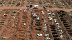 Petugas dengan pakaian pelindung membawa peti mati seseorang yang meninggal karena komplikasi COVID-19 ke dalam kuburan di pemakaman Vila Formosa di Sao Paulo, Brasil, Rabu (7/4/2021). Sao Paulo pada Rabu mulai menggali 600 kuburan tambahan setiap hari di pemakaman kotanya. (AP Photo/Andre Penner)