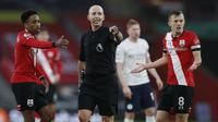 Dua pemain Southampton, bek Kyle Walker-Peters (kiri) dan kapten James Ward-Prowse, memprotes wasit Mike Dean dalam laga lanjutan Liga Inggris pekan ke-14 melawan Manchester City di St. Mary's Stadium, Southampton, Sabtu (19/12/2020). Southampton kalah 0-1 dari Manchester City.(AFP/Paul Childs/Pool)