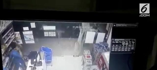 Kejadian horor terekam CCTV dimana pintu minimarket tiba-tiba terbanting ke arah luar dan pecah.