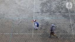 Seorang siswa didampingi orang tuanya tiba di SDN 05 Kalisari, Jakarta, Senin (30/8/2021). Pemprov DKI Jakarta menggelar pembelajaran tatap muka di tengah pandemi covid-19 mulai 30 Agustus 2021 secara terbatas dengan kapasitas 50 persen pada setiap satuan pendidikan. (Liputan6.com/Herman Zakharia)