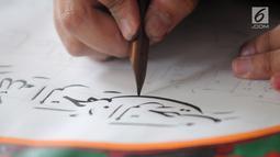 Peserta membuat kaligrafi kategori mushaf Alquran pada lomba MTQ Tingkat Kota Tangerang Selatan, Banten, Selasa (18/9). Nantinya, para juara MTQ Tingkat Kota Tangerang Selatan dibina agar dapat berprestasi di tingkat nasional. (Merdeka.com/Arie Basuki)