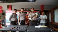 Kapolres Bangkalan, AKBP Anissullah M Ridha menunjukkan barang bukti senapan angin dan senjata tajam yang digunakan menganiyaan Sirin. (Liputan6.com/Musthofa Aldo)