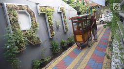 Pedagang melintas di salah satu gang kampung hijau di kawasan Malakasari, Jakarta, Sabtu (15/9). Tingginya kesadaran masyarakat akan pentingnya tumbuhan membuat kawasan tersebut terlihat asri dan dipenuhi berbagai tanaman. (Liputan6.com/Immanuel Antonius)