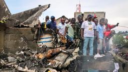 Tim penyelamat berkumpul setelah sebuah pesawat jatuh di kawasan padat penduduk, Goma, Republik Demokratik Kongo, Minggu (24/11/2019). Pesawat tersebut sedianya menuju ke Beni, 350 kilometer di utara Goma. (AP Photo/Justin Kabumba)