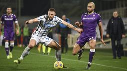 Gelandang Fiorentina, Sofyan Amrabat berebut bola dengan bek Inter Milan, Milan Skriniar pada lanjutan laga Liga Italia di Stadion Artemio Franchi, Sabtu dinihari WIB (6/2/2021). Inter mengalahkan Fiorentina 2-0 dan menggusur AC Milan dari puncak klasemen Serie A. (Massimo Paolone/LaPresse via AP)