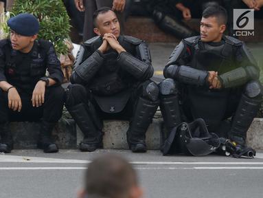 Personil kepolisian dari satuan Brimob beristirahat saat menjaga aksi unjuk rasa yang dilakukan Gerakan Nasional Kedaulatan Rakyat di depan Gedung Bawaslu, Jakarta, Selasa (21/5/2019). Ribuan aparat keamanan gabungan diterjunkan untuk mengamankan jalannya aksi. (Liputan6.com/Helmi Fithriansyah)