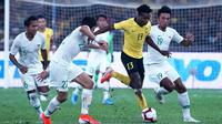 Pemain Timnas Malaysia, Mohamadou Sumareh (13), dikepung pemain Timnas Indonesia dalam laga Grup G kualifikasi Piala Dunia 2022 zona Asia di Stadion Nasional, Bukit Jalil (19/11/2019). (AFP/Kamarul Akhir))