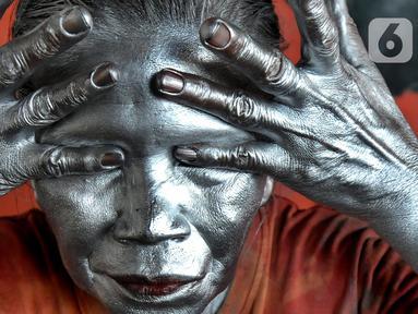 Pagi jelang siang pada  sudut toko perempatan lampu merah,  Nenek Mumum mulai merias wajah dan tubuhnya dengan cat silver. (merdeka.com/Arie Basuki)