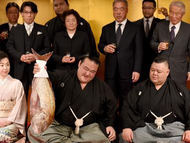 Pegulat sumo Jepang, Kisenosato foto bersama saat mendapat hidangan ikan red sea bream merayakan kemenangannya dalam upacara yang berlangsung di Tokyo, Jepang, Rabu (25/1). (AFP Photo/Toru Yamanaka)