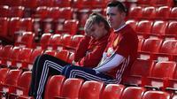 Supporter Manchester United tampak kecewa usai tim kesayangannya ditahan imbang Stoke 1-1. Hasil ini membuat Setan Merah tertahan pada posisi keenam klasemen Premier League. (Reuters/Russell Cheyne)