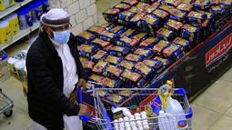 Seorang pria berbelanja bahan makanan dan persediaan saat mereka mempersiapkan diri seminggu menjelang bulan suci Ramadan di supermarket di ibu kota Yaman, Sanaa, Selasa (6/4/2021). (AFP Photo/Mohammed Huwais)
