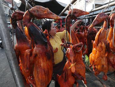 Pedagang menyiapkan babi panggang untuk perayaan Tahun Baru Imlek di Phnom Penh, Kamboja, Jumat (24/1/2020). Babi panggang menjadi menu santapan wajib bagi warga Tionghoa yang merayakan Imlek. (AP photo/Heng Sinith)