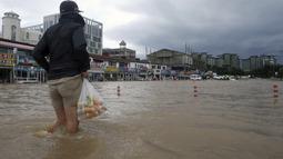 Seorang warga berjalan melewati banjir di Gangneung, Korea Selatan, Kamis (3/9/2020). Lebih dari 2.200 orang dievakuasi ke tempat penampungan sementara. (Lee Hae-yong/Yonhap via AP)