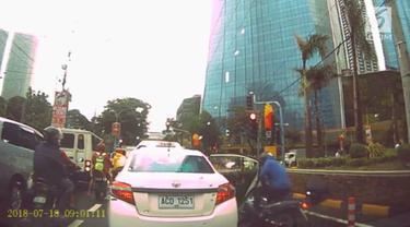 Seorang pengendara motor menabrak pintu mobil taksi yang dibuka mendadak. Insiden ini terjadi di persimpangan jalan kota Taguig, Filipina.
