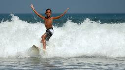 Natan Bontje selama latihan di pantai Kuta dekat Denpasar di pulau resor Indonesia Bali (6/5). Natan berusia sembilan tahun merupakan peserta termuda yang mengikuti kompetisi Asian Surfing Tour 2018 yang telah berakhir. (AFP Photo/Sonny Tumbelaka)