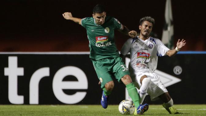 Gelandang PSS Sleman, Brian Ferreira, berebut bola dengan bek Arema FC, Alfin Tuasalamony, pada laga Liga 1 2019 di Stadion Maguwoharjo, Sleman, Rabu (15/5). PSS menang 3-1 atas Arema. (Bola.com/Yoppy Renato)