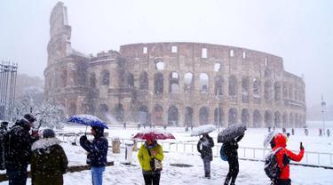 Sejumlah wisatawan mengabadikan Colosseum kuno saat hujan salju di Roma, Italia (26/2). (AFP Photo/Vicenzo Pinto)