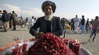 Seorang pria menjual buah delima di taman umum selama perayaan Nowruz, Tahun Baru Persia, di Kabul, Afghanistan, (21/3). Nowruz dirayakan pada hari pertama musim semi di negara-negara termasuk Afghanistan, Tajikistan, dan Iran. (AP Photo/Massoud Hossaini)