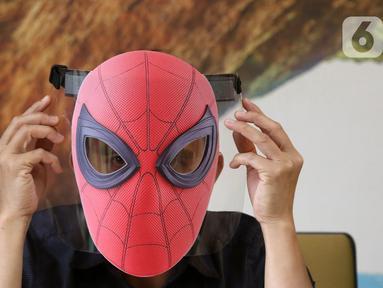 Pekerja memakai face shield atau pelindung wajah karakter Spiderman di Percetakan Bintang Sempurna, Bendungan Hilir, Jakarta, Rabu (24/6/2020). Pelindung wajah karakter tersebut dibanderol dengan harga Rp 35 ribu hingga Rp 50 ribu per buah. (Liputan6.com/Angga Yuniar)