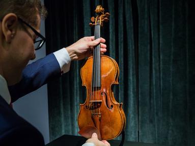 Perwakilan dari Sotheby Hong Kong memegang biola langka 1684 buatan Antonio Stradivari saat diperkenalkan di hadapan pers di Hong Kong (21/2). Pelelangan biola ini akan digelar pada 28 Maret 2017 mendatang di London. (AFP Photo / Isaac Lawrence)