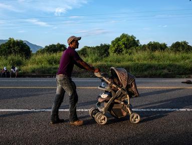Seorang imigran Honduras mendorong kereta bayi dalam perjalanannya menuju Amerika Serikat di negara bagian Oaxaca, Meksiko, 29 Oktober 2018. Kereta dorong bayi telah menjadi barang mewah bagi para imigran dalam perjalanan mereka. (Guillermo Arias/AFP)