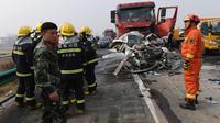 Petugas pemadam kebakaran dikerahkan ke lokasi kecelakaan beruntun 30 kendaraan di jalan raya dekat Yingshang, China timur, Rabu (15/11). Tak hanya mobil penumpang ukuran sedang saja yang terbakar hangus melainkan juga beberapa unit truk. (STR / AFP)