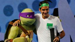 Petenis Swiss, Roger Federer berpose dengan salah satu karakter kura - kura ninja di Melbourne Park, Australia, (16/1). Acara ini juga sebagai kampanye penyelenggaraan Turrnamen  tenis Australia Terbuka yang dimulai 18 januari 2016. (REUTERS / Issei Kato)