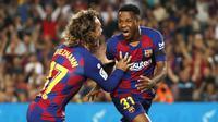 Pemain Barcelona, Ansu Fati, bersama Antoine Griezmann merayakan gol yang dicetak ke gawang Valencia pada laga La Liga di Stadion Camp Nou, Sabtu (14/9). Barcelona menang 5-2 atas Valencia. (AP/Joan Monfort)