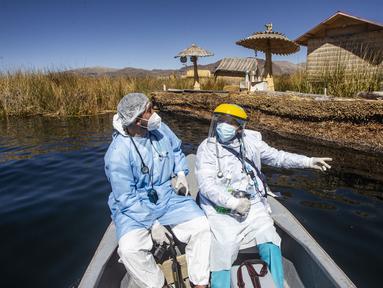 Petugas kesehatan diantar ke pulau Uros untuk menyuntik warga dengan vaksin COVID-19 Sinopharm, di danau Titicaca di Puno, Peru, pada 7 Juli 2021. Peru memulai vaksinasi COVID-19 untuk ratusan penduduk asli yang tinggal di pulau terapung Uros, di Danau Titicaca. (Carlos MAMANI / AFP)