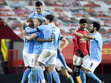 Para pemain Manchester City merayakan gol yang dicetak oleh Fernandinho ke gawang Manchester United pada laga Piala Liga Inggris di Stadion Old Trafford, Rabu (6/1/2021). City menang dengan skor 2-0. (Peter Powell/Pool via AP)