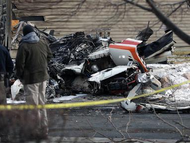Warga melihat puing-puing pesawat pribadi yang jatuh di kawasan perumahan Roy, Utah, Amerika Serikat, Rabu (15/1/2020). Seorang pilot berusia 64 tahun dilaporkan tewas. (Ben Dorger/Standard-Examiner, via AP)