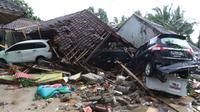 Dua unit mobil tertimbun reruntuhan rumah yang rusak setelah tsunami menerjang kawasan Anyer, Banten, Minggu (23/12). Data sementara jumlah korban dari bencana tsunami di Selat Sunda tercatat 168 orang meninggal dunia. (Liputan6.com/Angga Yuniar)