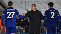 Manajer tim Leicester City, Brendan Rodgers (tengah) menyalami bek Timothy Castagne (kiri) usai berakhirnya laga lanjutan Liga Inggris 2020/21 pekan ke-19 melawan Chelsea di King Power Stadium, Leicester, Selasa (19/1/2021). Leicester City menang 2-0 atas Chelsea. (AFP/Rui Vieira/Pool)