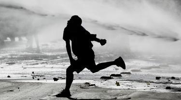 Demonstran antipemerintah melempar polisi dengan batu saat disemprot meriam air saat protes di Santiago, Chile, Jumat (27/12/2019). Chile terus bergolak menyusul demonstrasi memprotes kenaikan tarif kereta bawah tanah sejak 18 Oktober lalu. (AP Photo/Fernando Llano)