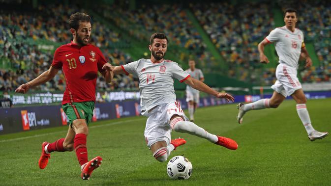 Bek Spanyol, Gaya berusaha menghalau bola yang dibawa gelandang Portugal, Bernardo Silva pada pertandingan persahabatan di stadion Jose Alvalade di Lisbon, Rabu (7/10/2020). Spanyol bermain imbang 0-0 atas Portugal. (AP Photo/Armando Franca)