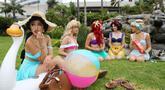 Cosplay putri-putri Disney duduk di luar San Diego Comic-Con, San Diego, California, Amerika Serikat, Jumat (20/7). Lebih dari 100 ribu cosplay diharapkan mengikuti konvensi komik dan hiburan tahunan ini. (Mario Tama/Getty Images/AFP)