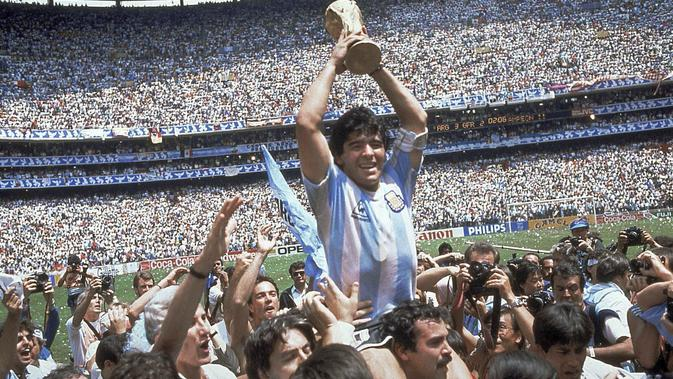 Diego Maradona memegang trofi timnya setelah Argentina menang 3-2 atas Jerman Barat pada pertandingan final Piala Dunia di Stadion Azteca di Mexico City. Maradona meninggal karena serangan jantung pada Rabu, 25 November 2020, di rumahnya di Buenos. Aires.