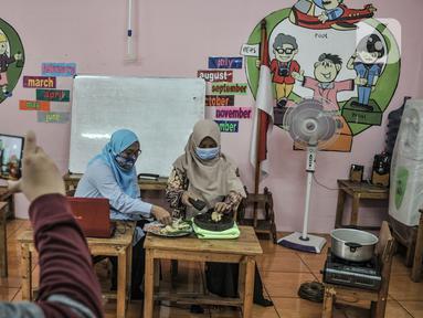 Pendidik mempraktikan pembuatan bir pletok saat kelas sentra memasak via virtual di Pendidikan Anak Usia Dini (PAUD) Cempaka, Tebet Barat, Jakarta, Senin (23/11/2020). Selama pandemi Covid-19, pendidik di PAUD Cempaka rutin menggelar kegiatan belajar secara virtual. (merdeka.com/Iqbal S Nugroho)