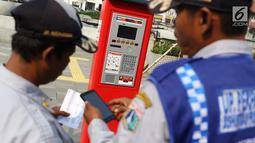 Petugas mengoperasikan mesin parkir meter di kawasan Kota Tua, Jakarta, Rabu (18/7). Sebanyak 13 Terminal Parkir Elektronik (TPE) dipasang di kawasan tersebut guna mengantisipasi membludaknya kendaraan yang parkir. (Liputan6.com/Immanuel Antonius)