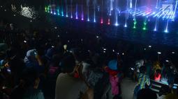 Warga mengabadikan gambar air mancur menari di Lapangan Banteng, Jakarta, Sabtu (11/8). Air mancur menari Lapangan Banteng diputar mulai pukul 18.30, 19.30, dan 20.30 WIB. (Merdeka.com/Imam Buhori)
