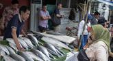 Pedagang ikan bandeng melayani pembeli di kawasan Rawa Belong, Jakarta, Selasa (21/1/2020). Bandeng yang biasanya menjadi hidangan khas saat Tahun Baru Imlek tersebut mulai ramai diperdagangkan di Rawa Belong. (Liputan.com/Faizal Fanani)